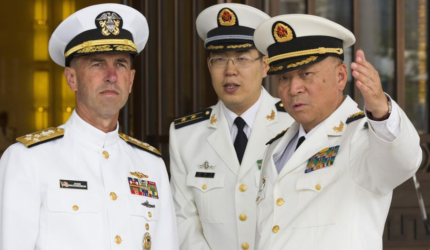FILE - In this Monday, July 18, 2016, file photo, U.S. Chief of Naval Operations Adm. John Richardson, left, listens to Commander of the Chinese Navy Adm. Wu Shengli, right, at Chinese Navy Headquarters in Beijing. The top U.S. admiral said friendly exchanges with China's navy are conditional on safe and professional interactions at sea. Richardson's comments Wednesday, July 20, 2016, follow several fractious encounters between the two sides' ships and planes in and over the disputed South China Sea. (AP Photo/Ng Han Guan, Pool, File)