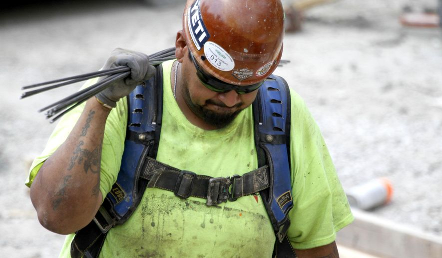 A construction worker carries rebar through a luxury apartment site during the heat of the day, Wednesday, July 20, 2016, in Chicago. The Occupational Safety and Health Administration urged employers to protect laborers doing construction, road and agricultural work, as high temperatures and humidity will affect the central United States this week, sending heat indexes as high as 115 degrees in some places for the first time this year. (AP Photo/Tae-Gyun Kim)