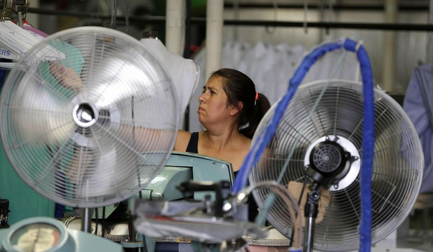 Gabby Crespo tries to keep cool while running a shirt press that creates a lot of heat at Wolf's Cleaners, Wednesday, July 20, 2016, in Milwaukee. High temperatures and humidity will bake much of the central United States this week, sending heat indexes soaring as high as 115 degrees in some places for the first time this year. (Rick Wood/Milwaukee Journal-Sentinel via AP)