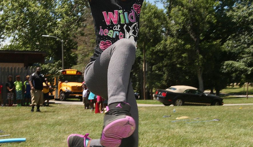 In this June 29, 2016 photo, Alazia Dickens clears a hurdle on an obstacle course during Boys and Girls Club and Decatur Park District partnership activities at Fairview Park in Decatur, Ill. The Boys and Girls Club will visit a different park each Wednesday this summer through the partnership with the park district to try out various sports and amenities. (Jim Bowling/Herald & Review via AP)