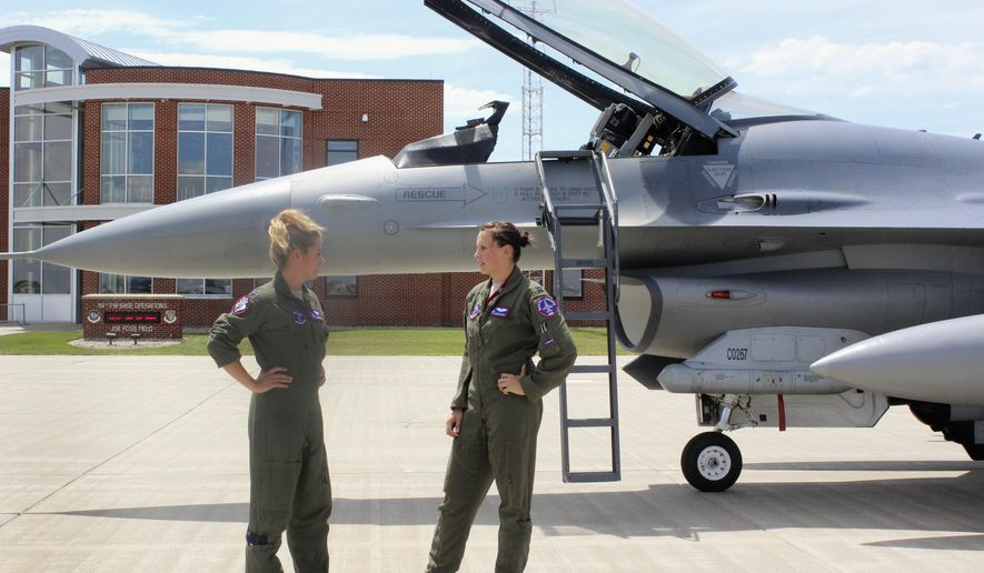 In this Tuesday, July 19, 2016, photo, Capt. Valerie Vanderostyne, left, and Capt. Shanon Davis, both with the South Dakota Air National Guard, chat alongside an F-16 Fighting Falcon at Joe Foss Field in Sioux Falls, S.D. The two are part of a select group of five women from around the country who can pilot F-16 fighter jets. Vanderostyne and Davis are the first two female fighter pilots that have been with the South Dakota Air National Guard in its 70-year history. (AP Photo/Regina Garcia Cano)