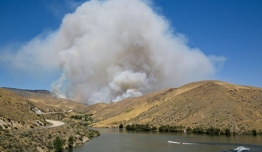 A large wildfire burns behind Lucky Peak Reservoir in Boise, Idaho, Tuesday, July 19, 2016. A tack room, chicken coop and wood shack all burned Tuesday afternoon in a fast-moving fire along Idaho State Highway 21, said Mary Lewerenz, the owner of the structures. Officials had closed State Highway 21 in both directions but reopened Tuesday night, with pilot cars leading traffic through the area.  (Kyle Green/The Idaho Statesman via AP)