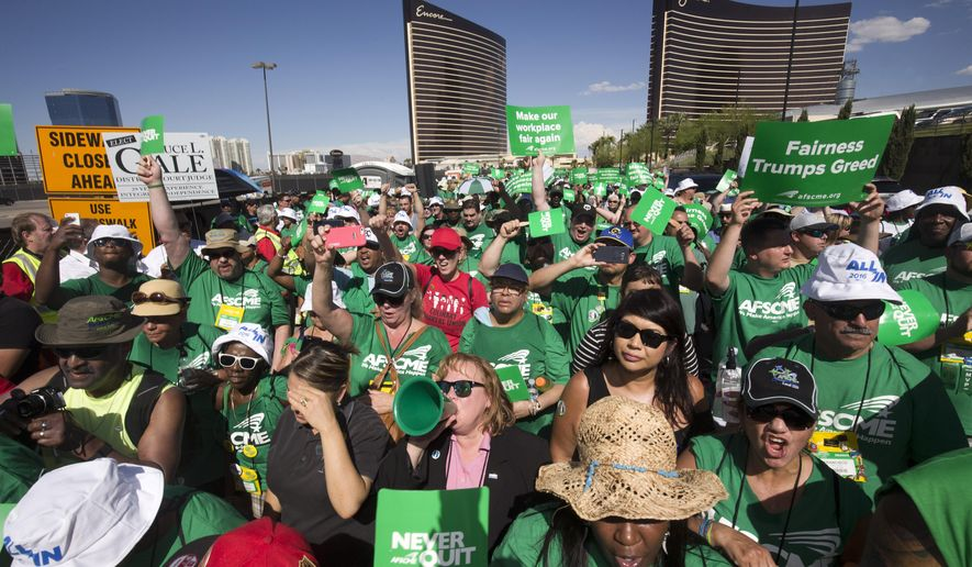 American Federation of State, County and Municipal Employees (AFSCME) union members picket near the Trump International Hotel Las Vegas during a union protest in Las Vegas, Wednesday, July 20, 2016. AFSCME members, in Las Vegas for a convention, came out in support of the Culinary Workers Union, Local 226, which is trying to unionize workers at the hotel. (Steve Marcus/Las Vegas Sun via AP)