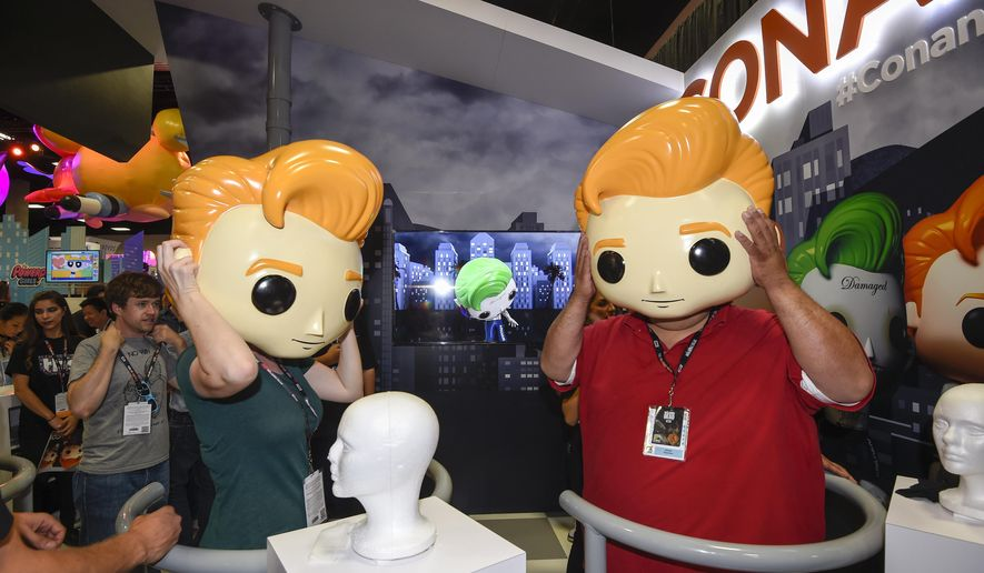 Fans try on plastic Conan O'Brien heads during Preview Night at Comic-Con International held at the San Diego Convention Center Wednesday July 20, 2016 in San Diego.  (Photo by Denis Poroy/Invision/AP)