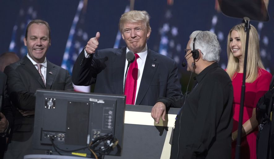 Republican presidential candidate Donald Trump, center, gives a thumbs up as he talks with production crew during a walk through in preparation for his speech at the Republican National Convention, Thursday, July 21, 2016, in Cleveland. At right is is daughter Ivanka. (AP Photo/Evan Vucci)