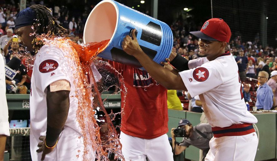 Boston Red Sox's Hanley Ramirez, left, is doused by Xander Bogaerts, right, after defeating the San Francisco Giants 11-7 at Fenway Park, Wednesday, July 20, 2016, in Boston. Ramirez hit three home runs in the game. (AP Photo/Charles Krupa)