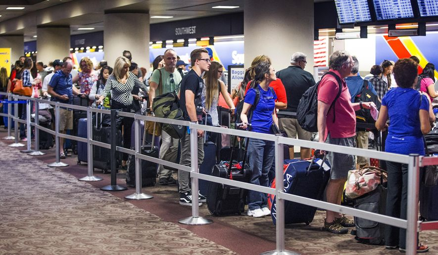 People wait in the Southwest Airlines check-in line at Sky Harbor International Airport, Thursday, July 21, 2016, in Phoenix. Southwest said it has mostly fixed computer problems that caused hundreds of flights to be canceled or delayed, but the airline warned passengers that there could be long lines at airports on Thursday. (Tom Tingle/The Arizona Republic via AP)