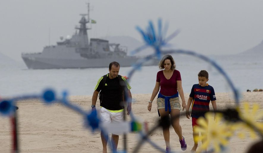 A family walks on the shore of Copacabana beach backdropped by a Brazilian navy vessel, in Rio de Janeiro, Brazil, Thursday, July 21, 2016. Brazilian police arrested 10 people who allegedly pledged allegiance to the Islamic State group on social media and discussed possible attacks during the Rio de Janeiro Olympics, officials said Thursday. (AP Photo/Silvia Izquierdo)