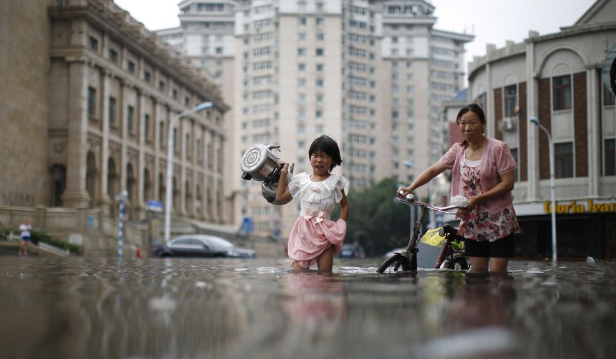 In this Wednesday, July 20, 2016 photo, a child carries kettles through a flooded street with a woman in Tianjin, China. China says dozens of people have died or gone missing since Monday in massive floods across the country's north. (Chinatopix via AP)
