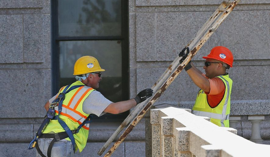 Dariusz Krupa, left, and German Arechar, right, of Mark 1 Restoration, a sub-contractor to JE Dunn, work at building a scaffolding at the state Capitol in Oklahoma City, Thursday, July 21, 2016.  The elaborate scaffolding system has started to go up on the north side of Oklahoma's nearly 100-year-old state Capitol, signaling that a multi-year project to renovate and update the building for its next century is getting underway.  (AP Photo/Sue Ogrocki)