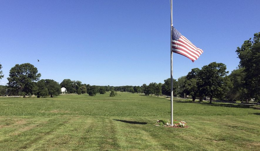 "In this Wednesday, July 20, 2016 photo, the flag flies at half-staff on the town green in Lebanon, Conn. The town has been unable to expand its library on the green because of an 18th century court decision the gives ownership of the mile-long green to the ""heirs and assigns"" of 51 original deed holders. Town historian Alicia Wayland estimates that could be about 10,000 people. (AP Photo/Pat Eaton-Robb)"