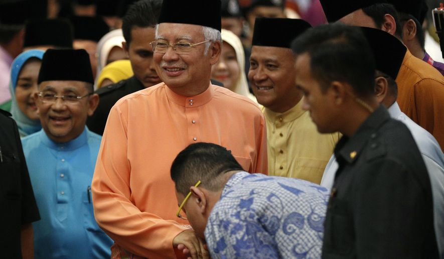 Malaysian Prime Minister Najib Razak, center, arrives for an Eid al-Fitr open house event in Kuala Lumpur, Malaysia, Thursday, July 21, 2016. Pressure mounted Thursday on Najib, with lawmakers demanding he go on leave and be held accountable after U.S. officials initiated action to seize more than $1 billion they say was stolen from a state investment fund by people close to the premier. (AP Photo/Vincent Thian)