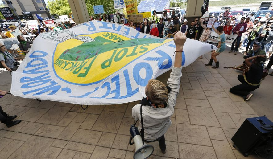 File--In this Thursday, May 12, 2016, file photograph, protesters wave a banner during an attempt to disrupt a federal auction of drilling rights at a hotel in Lakewood, Colo. More than 200 people turned out to protest the Bureau of Land Management sale. Documents released on Wednesday, July 19, 2016, show that undercover officers mingled with protesters to garner information and relay to police officials. (AP Photo/David Zalubowski, file)