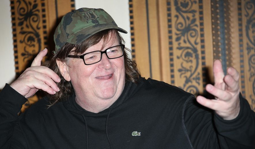 "In this June 9, 2016, file photo, director Michael Moore reacts as he poses for photographers at the photo call of his new film, 'Where To Invade Next' in London. Moore said during an online edition of HBO's ""Real Time with Bill Maher"" in July 20, 2016, that he thinks Republican Donald Trump is going to win the upcoming presidential election. (Photo by Joel Ryan/Invision/AP, File)"