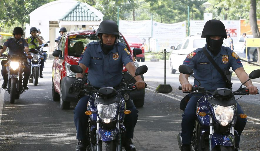 """Motorcycle-riding police officers patrol the compound of a Government hospital in the suburban Quezon city northeast of Manila, Philippines where former President Gloria Macapagal Arroyo is currently detained Wednesday, July 20, 2016. On Tuesday the Philippine Supreme Court ordered the dismissal of a plunder charge against her and ordered her immediate release from nearly five years of hospital detention. The release did not happen Wednesday due to certain """"procedural"""" technicalities. (AP Photo/Bullit Marquez)"""