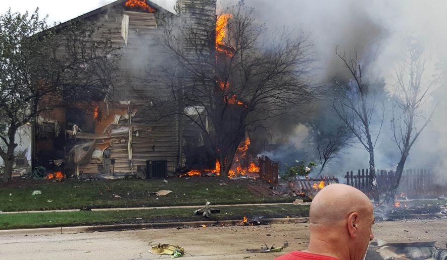 A home burns following a plane crash in Joliet, Ill., Thursday, July 21, 2016. (Suzanne Baker/Chicago Tribune via AP)