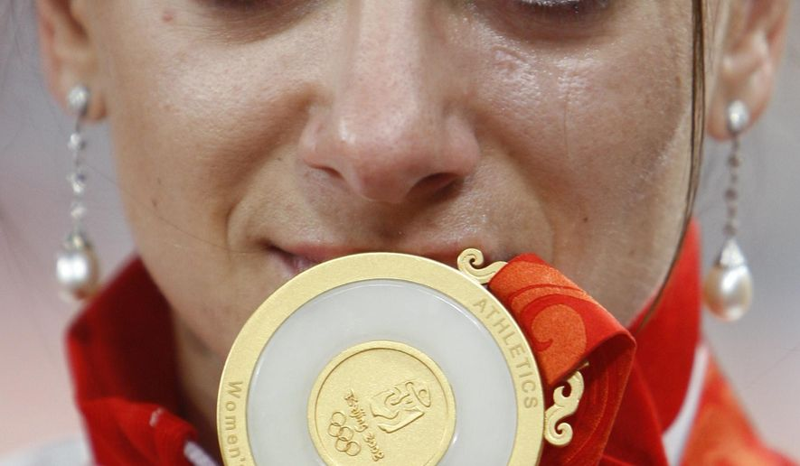 FILE - In this Aug. 19, 2008 file photo Russian pole vaulter Yelena Isinbayeva shows her gold medal during an awarding ceremony of the women's pole vault in the National Stadium at the Beijing 2008 Olympics in Beijing. The Court of Arbitration for Sport will issue its verdict Thursday, July 21, 2016 on Russia's appeal to overturn the IAAF ban on its track and field athletes for the 2016 Rio Olympic Games.  (AP Photo/Greg Baker, file)