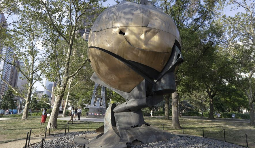 Pedestrians pass the Koenig Sphere in Battery Park Thursday, July 21, 2016, in New York. the Port Authority's Board of Commissioners approved plans to relocate the sphere back to the World Trade Center site. (AP Photo/Frank Franklin II)
