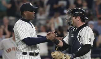 New York Yankees relief pitcher Aroldis Chapman, left, shakes hands with catcher Austin Romine after the Yankees defeated the San Francisco Giants 3-2 in a baseball game Friday, July 22, 2016, in New York. (AP Photo/Julie Jacobson)