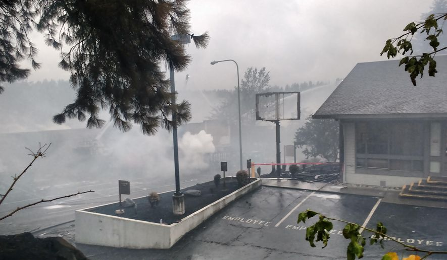 In this photo provided by Doug Esser, smoke rises Friday, July 22, 2016, from buildings damaged in a large overnight fire in Bothell, Wash. Officials said the fire started around 3 a.m. and was spread by high winds. (Doug Esser via AP)