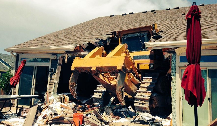 This photo provided by the Denver Police Department shows a bulldozer after crashing into a home.  Investigators say a man operating a bulldozer had a medical emergency that caused him to accidentally plow into a home in Denver. The Denver Post reports  the crash happened in the Green Valley Ranch neighborhood Friday, July 22, 2016. The driver, whose name and medical condition have not been released, suffered minor injuries. Capt. Greg Pixley with the Denver Fire Department says firefighters worked to shore up the home, which was unoccupied and has been condemned. The bulldozer demolished a deck, an exterior wall and part of the home's roof. (Denver Police Department via AP)