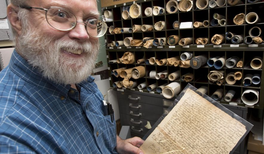 New Hampshire State Archivist Brian Burford poses with a 1726 deed from Widow Brustor at the state's archive vault Friday, July 22, 2016, in Concord, N.H. Bruford used the document at a workshop to help to teach volunteers how to transcribe Civil War-era letters and other documents in hopes that they will offer their services to local historical societies and other groups trying to preserve the state's history. (AP Photo/Jim Cole)