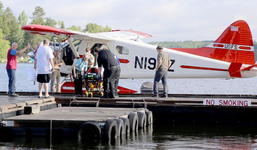 CORRECTS TO STATE CAMPERS WERE ALONG U.S.-CANADA BORDER- A camper is attended to by ambulance staff after arriving Thursday, July 21, 2016 in Ely, Minn., by floatplane from the Boundary Waters Canoe Area Wilderness after being injured following a severe storm that knocked trees down on Basswood Lake. The injured party received non-life threatening injuries and was treated at the Ely-Bloomenson Community Hospital.  A boy and a woman camping with a Boy Scouts adventure program were killed and two other campers were injured when severe storms swept through a remote area along the U.S.-Canada border. (Hailey Worth/Ely Echo Newspaper via AP)