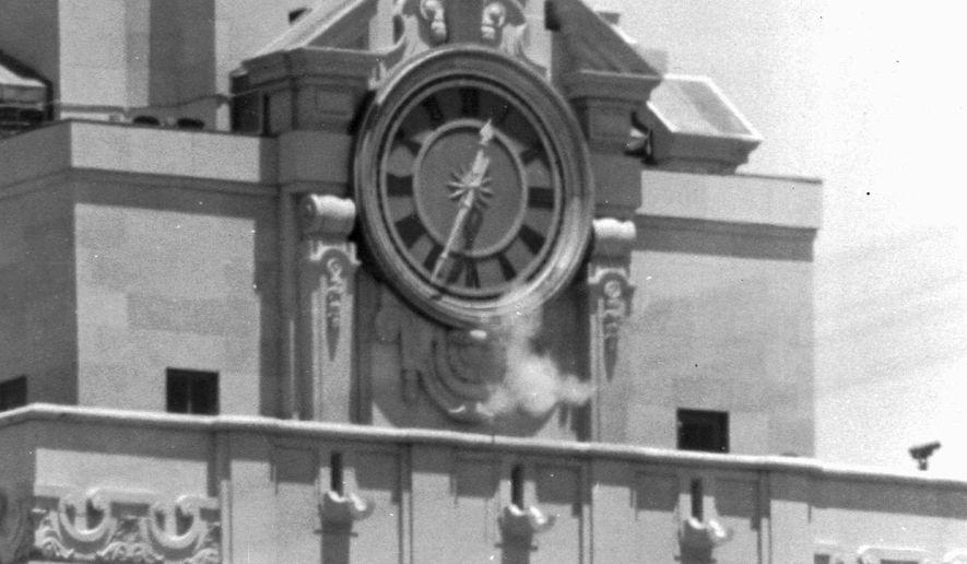 FILE -  In this Aug. 1, 1966 file photo, smoke rises from sniper Charles Whitman's gun as he fires from the tower of the University of Texas administration building on crowds below in Austin, Texas. This year marks the 50th anniversary of the shootings. (AP Photo, File)