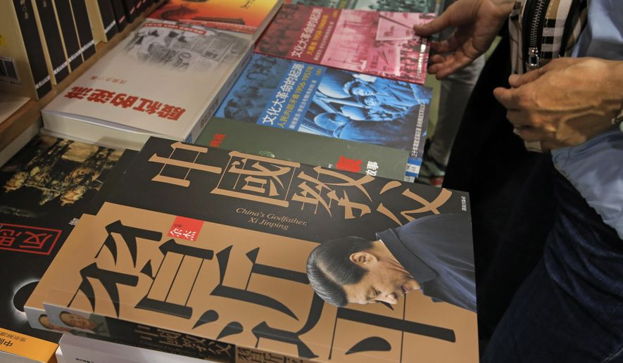 "In this Wednesday, July 20, 2016 photo, copies of ""China's Godfather Xi Jinping"" and other so-called banned books are on display at an annual book fair in Hong Kong. Hong Kong publishers unveiled their latest titles on sensitive Chinese topics at a major book fair this week even as many in the industry despaired over the chilling effect from the recent case of five missing booksellers. (AP Photo/Vincent Yu)"