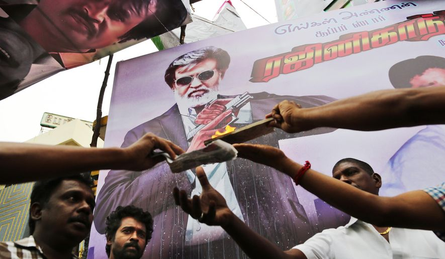 """Fans of Indian superstar Rajinikanth offer prayers outside a cinema before the screening of """"Kabali"""" in Chennai, India, Friday, July 22, 2016. Hundreds of thousands of fans of Indian superstar Rajinikanth are thronging cinemas across the country to catch the premiere of his latest film, """"Kabali"""". Sixty-five-year-old Rajinikanth is one of India's most popular star and counts millions of fans who speak the Tamil language and even those who don't. (AP Photo/Aijaz Rahi)"""