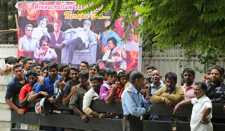 Fans of Indian actor Rajinikanth wait outside a theatre to buy tickets on the eve of release of his new movie Kabali, in Bangalore, India, Thursday, July 21, 2016. Businesses in southern India have given their employees the day off on Friday so they can attend screenings of a new film starring Tamil cinema's superstar Rajinikanth. One of Asia's highest paid actors, Rajinikanth is considered one of the most bankable stars in India. (AP Photo/Aijaz Rahi)