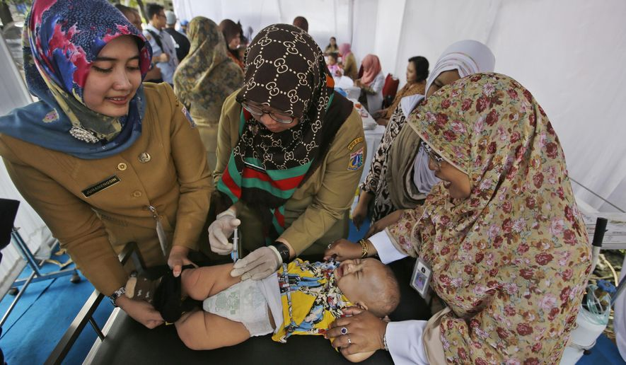 In this Monday, July 18, 2016, Indonesian health officials inject a baby during a revaccination program for children who were earlier given fake vaccines, at a community health center in Jakarta, Indonesia. Vials of counterfeit vaccines filled with saline solution and antibiotics have been discovered at 37 hospitals and clinics in nine cities, according to the Food and Drug Agency. So far, 23 people have been arrested, including three doctors. The number of affected children is still being investigated. (AP Photo/Achmad Ibrahim)