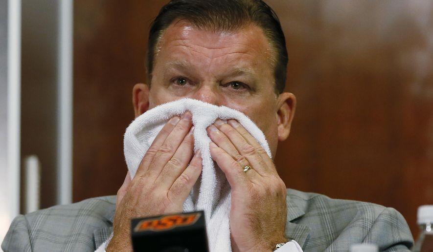 Oklahoma State basketball coach Brad Underwood wipes his face during a news conference in Stillwater, Okla., Friday, July 22, 2016. Oklahoma State basketball player Tyrek Coger died after a 40-minute team workout on the football stadium stairs in hot weather, Thursday, July 21, 2016. (AP Photo/Sue Ogrocki)
