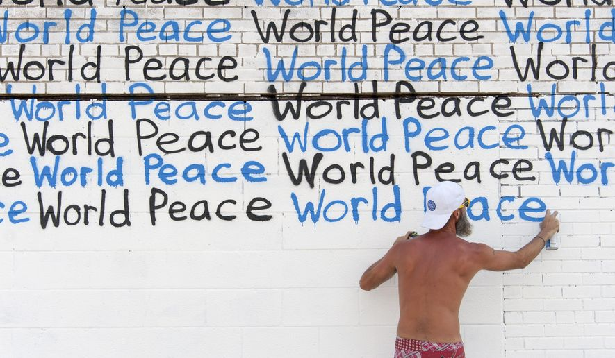 In this July 20, 2016 photo, Renda Writer creates a mural as part of his World Peace Mural Tour, at a building on the corner of Grand River and Rosa Parks Blvd. in Detroit. (David Guralnick / The Detroit News)/Detroit News via AP)