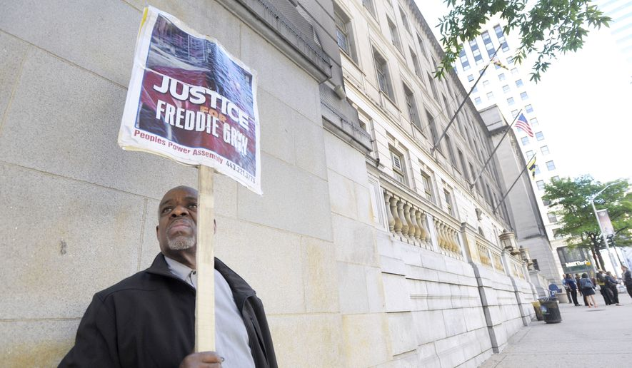 In this June 9, 2016, file photo, Arthur B. Johnson Jr., of Baltimore, demonstrates alone outside Baltimore's Courthouse East on the first day of the trial of Officer Caesar Goodson, one of six Baltimore city police officers charged in connection to the death of Freddie Gray, in Baltimore. More than a year after Freddie Gray's death, the same streets that exploded in fury and flame are calm. Despite back-to-back acquittals for officers charged in Gray's death, the physical protest movement that helped topple the careers of both the police commissioner and the mayor has dissipated, leaving activists exploring other avenues for change. (AP Photo/Steve Ruark, File)