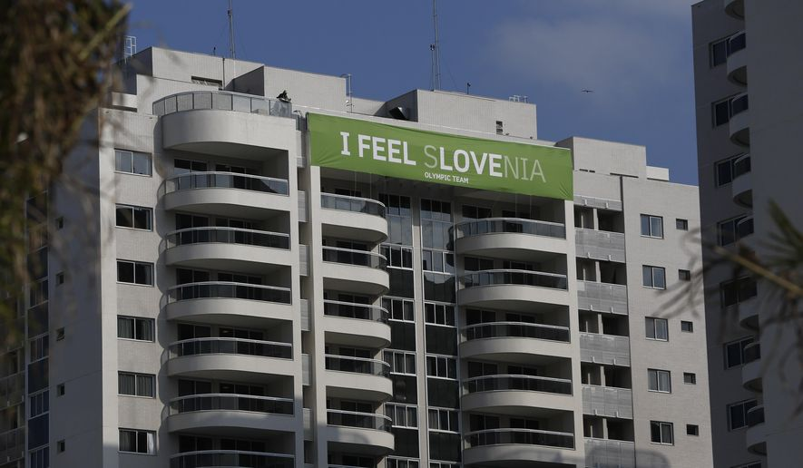 A banner of the Slovenia team hangs on the top of a building of the Olympic Village in Rio de Janeiro, Brazil, Saturday, July 23, 2016. The brand new complex of residential towers are where nearly 11,000 athletes and some 6,000 coaches and other handlers will sleep, eat and train during the upcoming games, that will kickoff on Aug. 5. (AP Photo/Leo Correa)