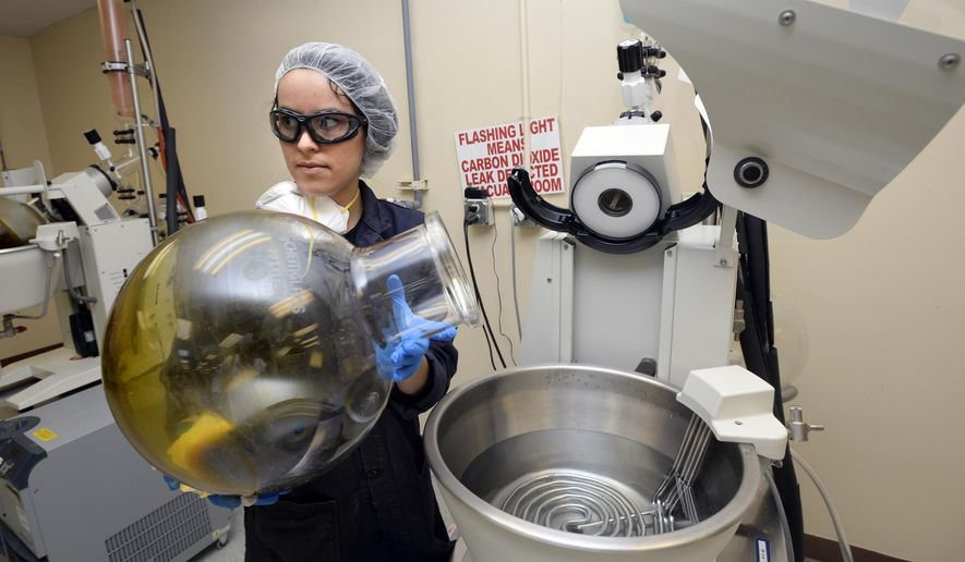 "ADVANCE FOR USE SATURDAY, JULY 23 - In this July 6, 2016 photo, Vanessa Cantu removes hemp oil from a hot water bath that evaporates and removes the isopropyl alcohol used to extract CBD, THC, phytochemicals and terpenes from the hemp plant at the CWHemp facilities in Boulder, Colo. Between 600 and 1,000 units of CW's product ship from the premises each month, extracted from a strain of the plant called Charlotte's Web, made famous by the 2013 Sanjay Gupta-hosted CNN documentary ""Weed."" (Paul Aiken/Daily Camera via AP)"