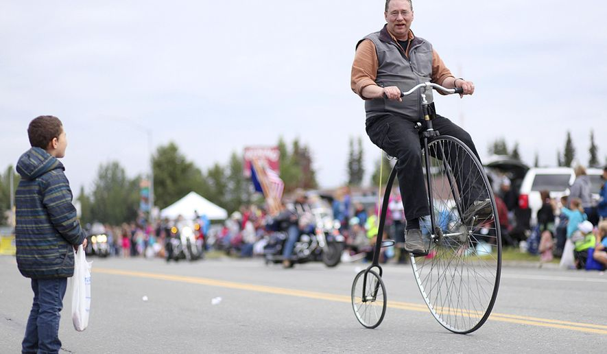 ADVANCE FOR RELEASE SATURDAY, JULY 23, 2016 AND THEREAFTER - In this July 4, 2016 photo, Doug Field demonstrates how to ride his penny-farthing bicycle during a Fourth of July Parade in Kenai, Alaska. Field's father purchased the bicycle, built by the now out-of-business Boneshaker company, on impulse in San Francisco in the 1970s. (Kelly Sullivan/Peninsula Clarion via AP)