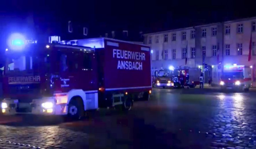 Fire trucks and ambulances stand in the city center of Ansbach, Germany, on Monday morning after a man was killed when an explosive device he was believed to be carrying went off near an open-air music festival, injuring 10 others. (News5 via Associated Press)