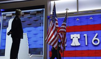 A worker carries flags across the main stage during preparations before the start of the 2016 Democratic Convention, Monday, July 25, 2016, in Philadelphia. (AP Photo/John Locher)