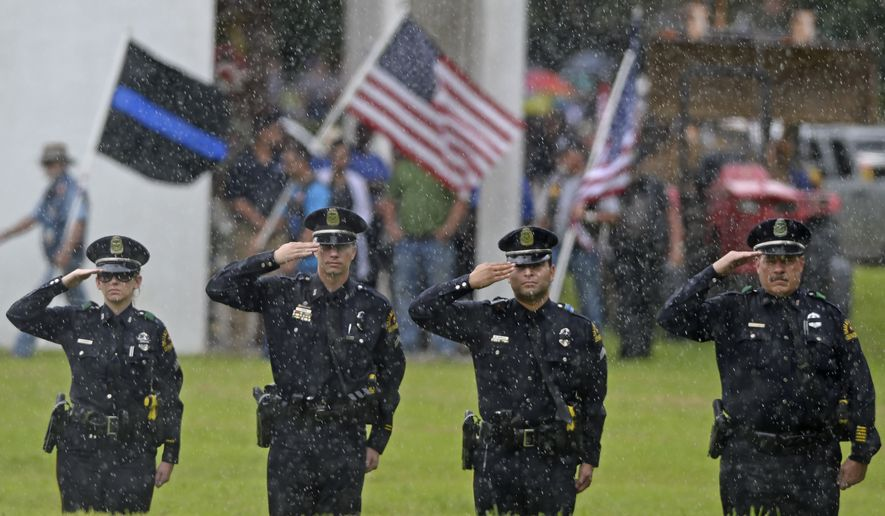 As rain falls, members of the Dallas Police Department salute as the casket carrying fallen Cpl. Montrell Jackson is removed from the hearse during funeral services in Baton Rouge, La., Monday, July 25, 2016. Jackson, slain by a gunman who authorities said targeted law enforcement, is the last of the three Louisiana law enforcement officers killed in last week's ambush to be buried. (Hilary Scheinuk/Baton Rouge Advocate via AP)