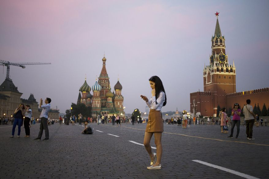 A young woman holds her smartphone at Red Square with the Kremlin's Spasskaya Tower, right, and St. Basil Cathedral, center, in the background in Moscow, Russia, Monday, July 25, 2016. (AP Photo/Pavel Golovkin)