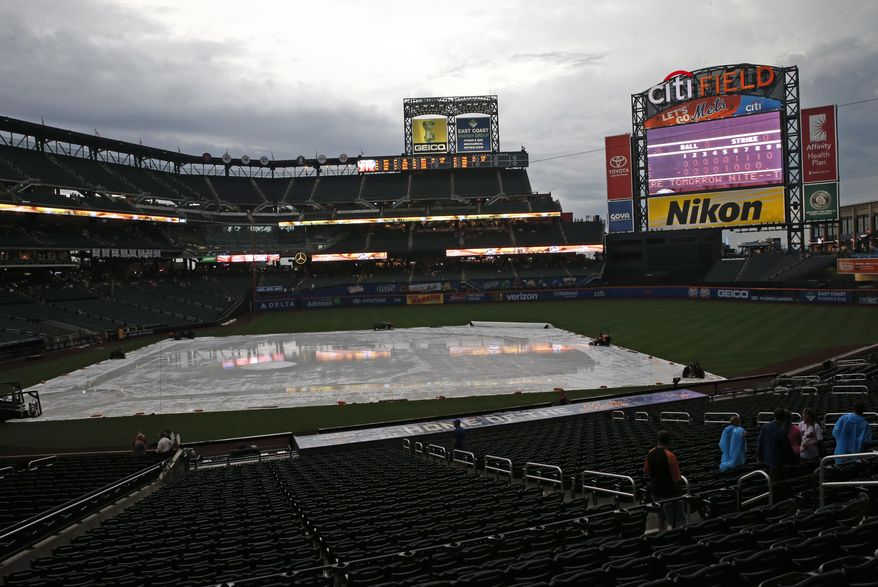 A tarp filled with rain sits on the field before a scheduled baseball game between the St. Louis Cardinals and the New York Mets, Monday, July 25, 2016, in New York. Monday's game was postponed due to rain and will be made up Tuesday as part of a doubleheader starting at 4 p.m. (AP Photo/Kathy Willens)