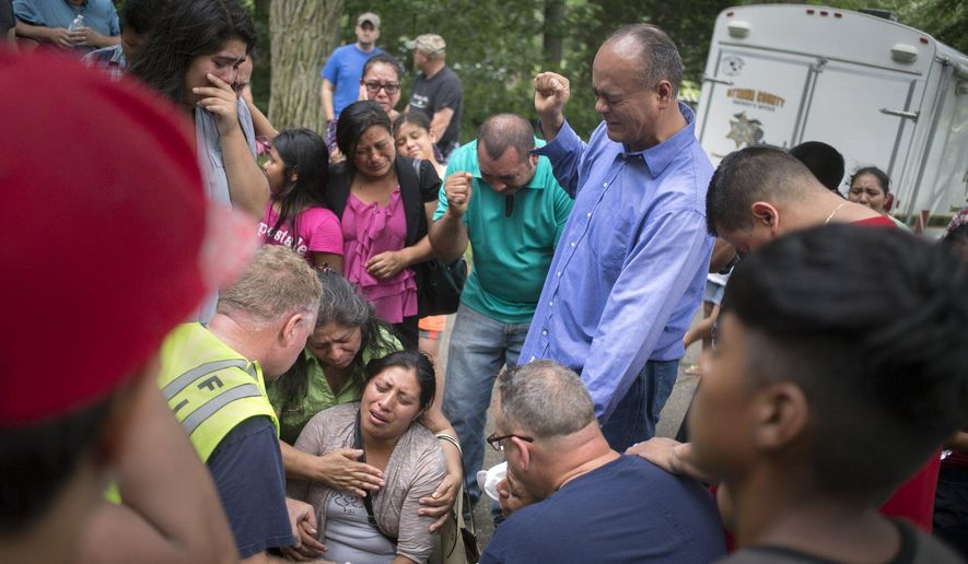 A family member of the victim who has drowned is aided by emergency personnel, church and other family members, while crying out in prayer after emergency personnel discovered the missing body at Crockery Lake in Chester Township, Mich., Sunday, July 24, 2016. (Tom Brenner/The Grand Rapids Press-MLive.com via AP)