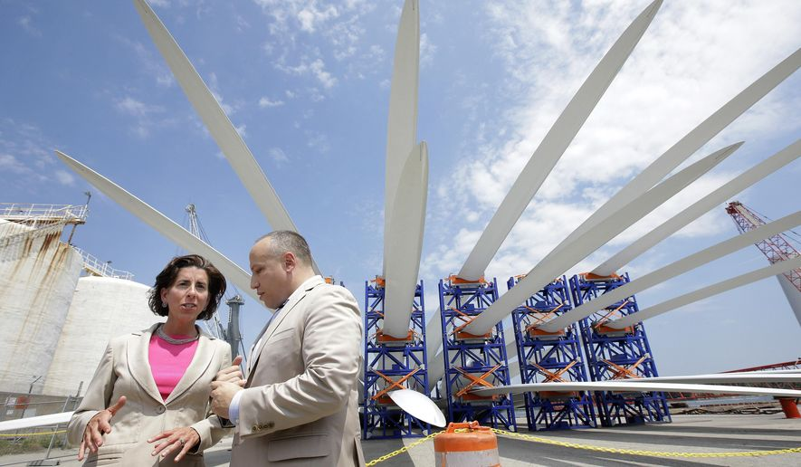 Rhode Island Gov. Gina Raimondo, left, speaks with Deepwater Wind CEO Jeffery Grybowski, right, while touring a staging site for the nation's first off-shore wind farm Monday, July 25, 2016, at Port of Providence, in Providence, R.I. Raimondo visited the site Monday to see the main components for the turbines before they are brought offshore. Wind turbine blades, background, sit in racks. (AP Photo/Steven Senne)
