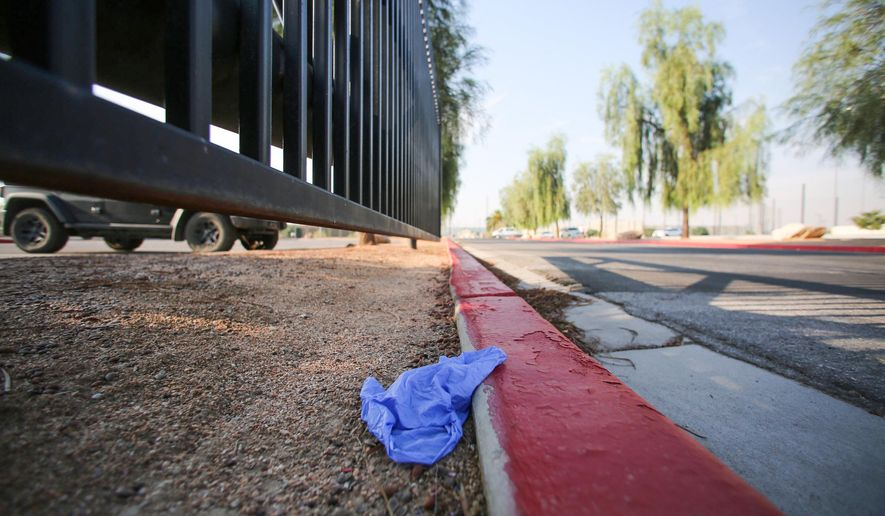 "A medical glove lies discarded on a curb at Big League Dreams park, near where police say a shooting erupted when a man in a vehicle attempted to rob a group of people playing ""Pokemon Go"" early Monday, July 25, 2016, in Las Vegas. According to police, a player and the suspect shot each other and both men have non-life threatening injuries. (Brett Le Blanc/Las Vegas Review-Journal via AP)"