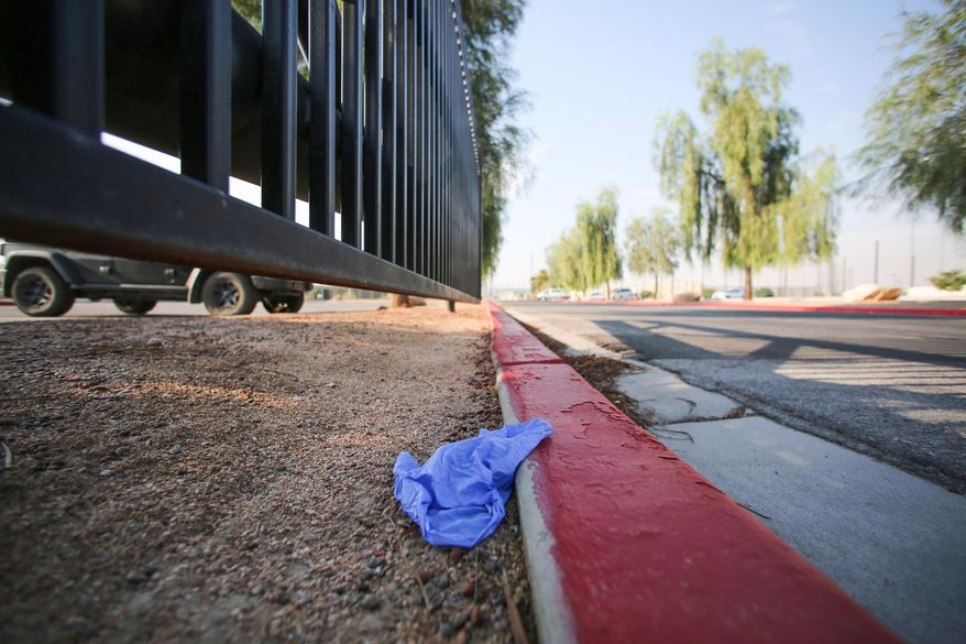 """A medical glove lies discarded on a curb at Big League Dreams park, near where police say a shooting erupted when a man in a vehicle attempted to rob a group of people playing """"Pokemon Go"""" early Monday, July 25, 2016, in Las Vegas. According to police, a player and the suspect shot each other and both men have non-life threatening injuries. (Brett Le Blanc/Las Vegas Review-Journal via AP)"""