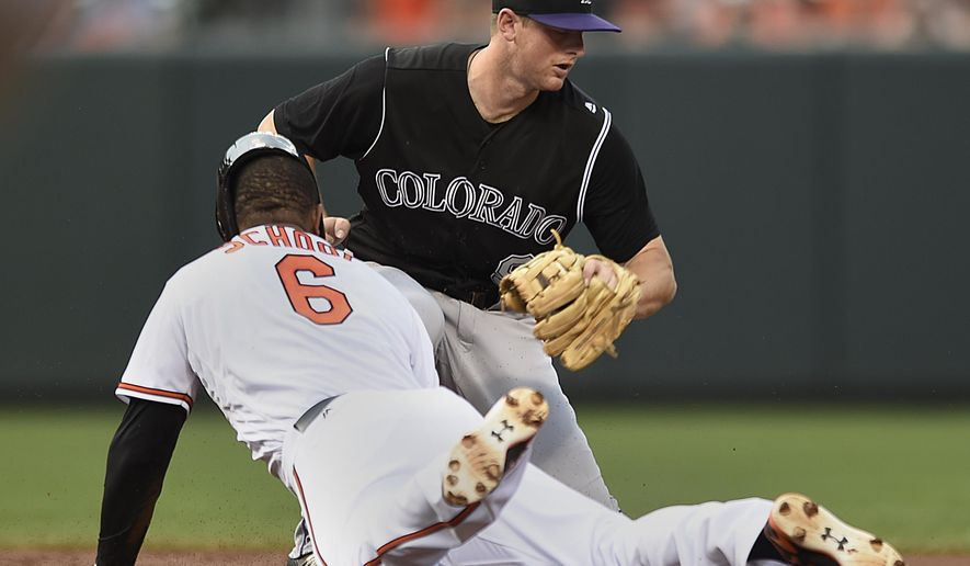 Baltimore Orioles' Jonathan Schoop slides safely into second for a double as Colorado Rockies shortstop Trevor Story takes the throw in the first inning of a baseball game, Monday, July 25, 2016 in Baltimore. (AP Photo/Gail Burton)