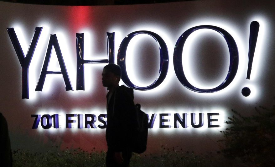 In this Nov. 5, 2014, file photo, a person walks in front of a Yahoo sign at the company's headquarters in Sunnyvale, Calif. Verizon bought Yahoo in a sale announced Monday, July 25, 2016. (AP Photo/Marcio Jose Sanchez, File)