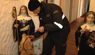 A police officer works with a K-9 inspecting the premises of Our Lady of the Rosary of Fatima monastery on the outskirts of Buenos Aires, Argentina. (Associated Press)